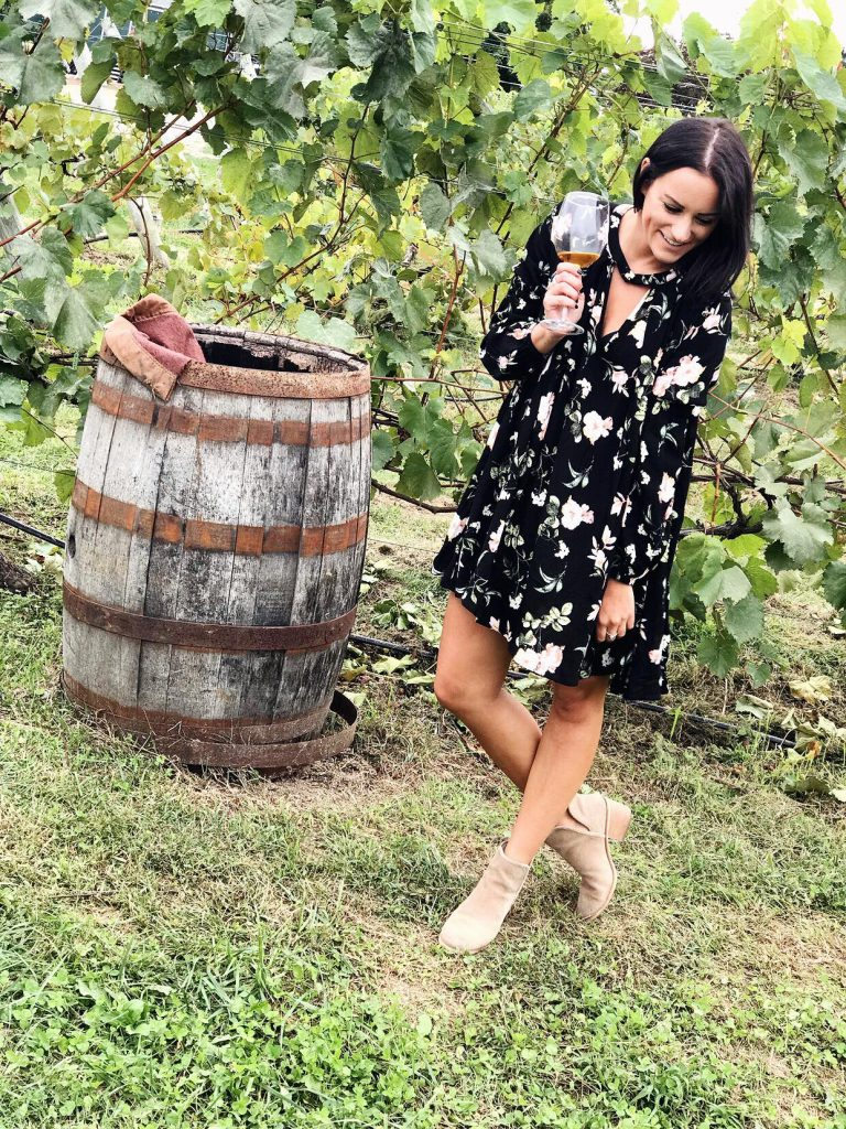 standing up at a winery drinking wine wearing a free people dupe dress