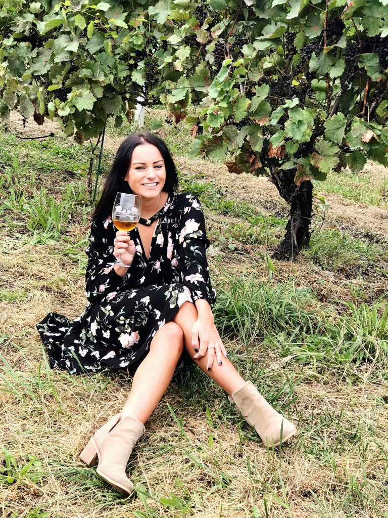 Wine tasting wearing a black free people dupe dress from amazon prime with flowers and tan low wedge booties
