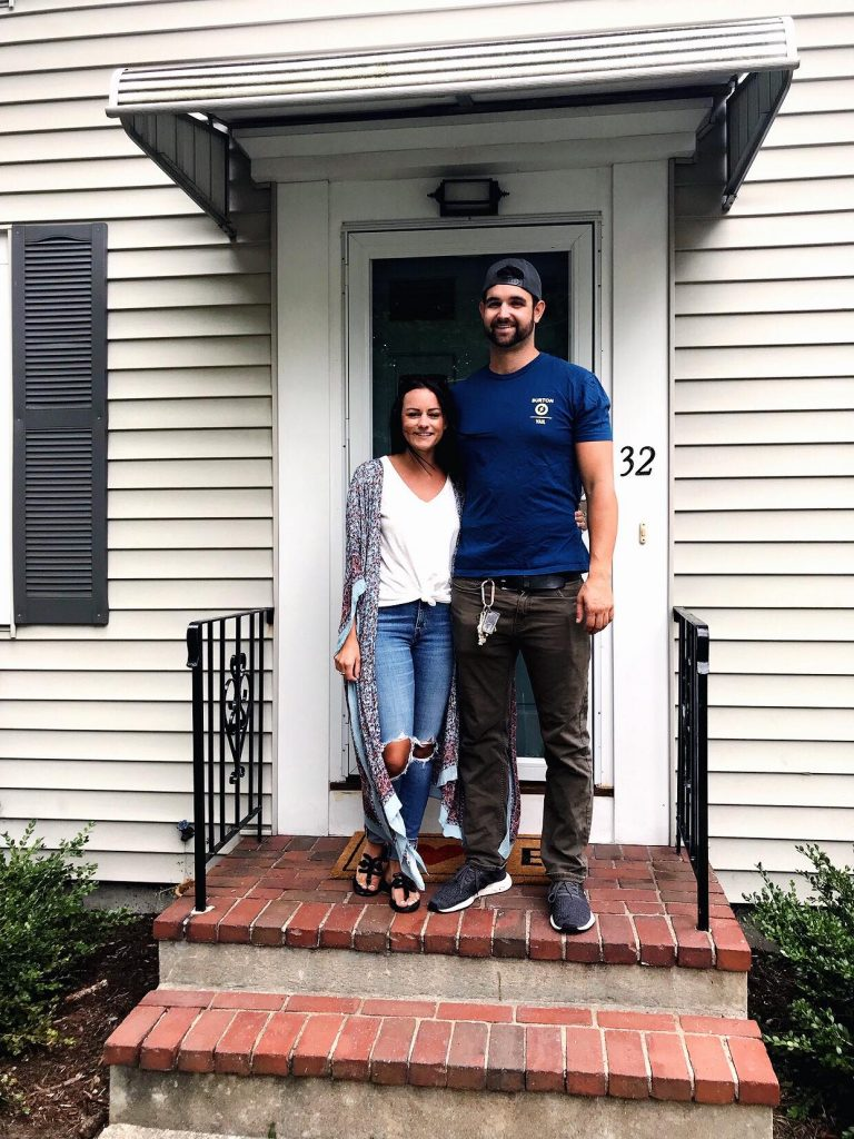 couple standing in front of new house that they just purchased