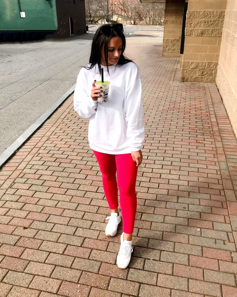 comfy loungewear outfit of red amazon leggings white sweatshirt and white reebok sneakers